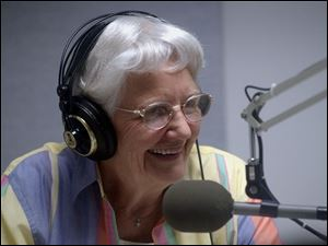 Volunteer Ethel Bradford reads the newspaper to listeners of the Sight Center Audio Network.