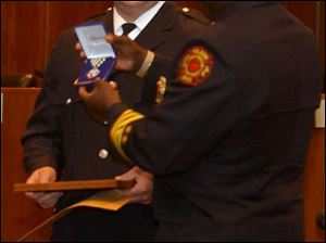 Toledo firefighter Scott Hathaway receives a Medal of Commendation from Fire Chief Mike Bell.