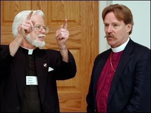 Father Jack Kimble, left, rector of All Saints Episcopal Church, talks with Bishop Mark Hollingsworth during Bishop Hollingsworth's first visit to Toledo after his April consecration as the 11th Episcopal bishop of Ohio. Bishop Hollingsworth, 50, met with more than 90 local clergy and lay leaders June 5 at All Saints Episcopal Church, 563 Pinewood, to hear their needs and expectations. 'It was marvelous. A very positive meeting,' Father Kimble said. The bishop is not due to make another episcopal visit to the Toledo area again until late in 2005.