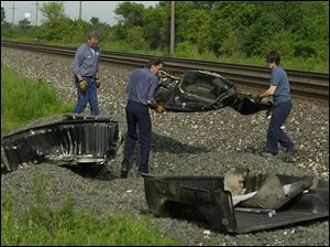 Workers remove debris from a vehicle that was struck by a train in Fulton County.