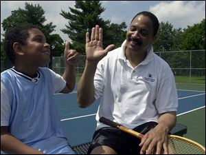 Johnny Mickler, 52, gets a thumbs-up from his 9-year-old son, Caleb, after sweating it out on the tennis courts.
