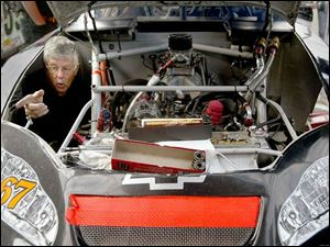 Harold Eaatmon works inside the engine compartment of Jason Jarrett's car in the pits before yesterday's ARCA event.