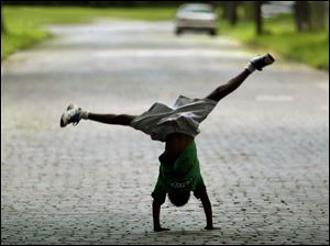 ROV cartwheel 01 -  MArquail Witherspoon, 8, does a cartwheel as he crosses Rosalind PL. to his aunt's home. Allan Detrich/The Blade