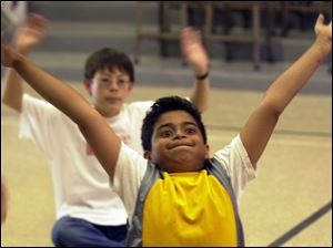 ROV commonspace02p 02 - 07/02/04- Nine-year-old Kiran Venkat, of Perrysburg, streches his arms and his face while preparing for a dance lesson at a creativity camp at Common Space Center for Creativity in Toledo Friday afternoon.  The camp included various painting, ceramic, and dance techniques and ended the week with an exhibition of work and preformance for parents.
