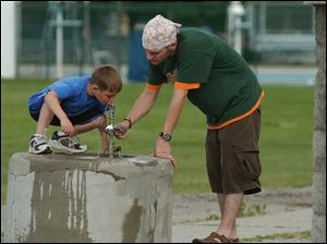 Seven year old Bryce Hess gets a helping hand for a drink of water from his older brother Ryan Hess at Delta Community Park Thursay afternoon. Lisa dutton 06/03/2004 NBR Delta rover .jpg