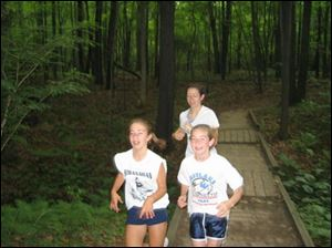 Coach Sarah White, rear, goes on the trail with Sylvania Striders team members McKenzie est, left, and Leah Zellers.