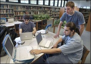Ethan Wilke, 19, seated from left, and Rob Bathurst work on school computers under the supervision of Don Hertzfeld.