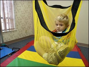 Mitchell Sworden, 3, enjoys a ride in a net swing during the 'play' time part of his session at the rehabilitation center.