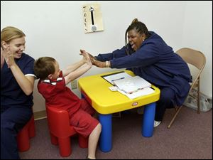Zackary Schroeder, 7, is praised by teachers MaryBeth Rentsch, left, and Phyllis Latimer after counting to 20 by twos.