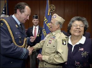 Brig. Gen. Dany Van de Ven jokes with Guadalupe Flores and his wife, Maria, after Mr. Flores was presented with the Fourragere, one of Belgium's most prestigious awards, for his military service. Mr. Flores participated in the Battle of the Bulge.