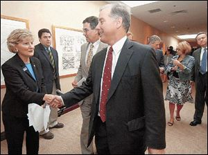 Ohio state Sen. Teresa Fedor shakes hands with former presidential candidate Howard Dean before attending a conference during the Democratic National Convention in Boston on independently auditable voting systems .