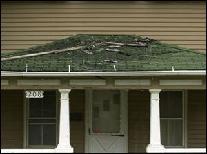 The roof and front porch are deteriorating on the abandoned house at 208 W. Garfield Ave.