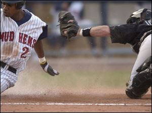 Nook Logan eludes the tag of Indianapolis catcher Mark Johnson in the third inning to score the Mud Hens' first run.