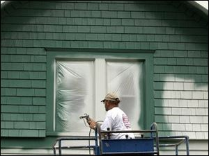 The thick liquid goes onto the exterior of a house much like traditional paint.