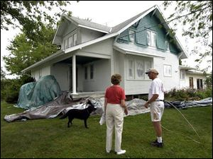 Jeanette Brandt, with Bob Koester of Spray On Siding, didn't want to cover the details of her 1920s-era bungalow. The thick liquid goes onto the exterior of a house much like traditional paint.