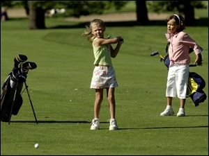 Abby Kalucki, 6, hits a fairway shot as Morgan Hall, 6, watches. The girls were playing during a junior clinic at Highland Meadows Golf Club.