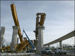 After the accident, the collapsed crane, left, is on the ground as its twin remains in place, right.