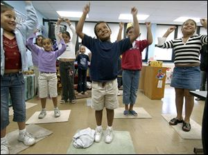 CTY migrant28p A  July 28, 2004-- Vanessa Aguayo,  left, Hector Mena, center, and Monica Gomez,  right, and classmates dance along with music teacher Julie Zedlitz during summer school for children of migrant workers. The three eight year-olds and their classmates were having fun learning Wednesday morning at the class in Delta. Blade photo by Andy Morrison