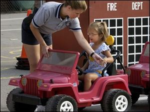 NBR July 21, 2004 - Maumee police officer Wendy Newsome shows Ashli Mengel, 4, the proper way to signal a left turn during the Maumee Safety City at Fort Miami School.   Blade photo by Dave Zapotosky  safety21p