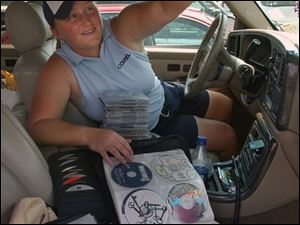 Meredith Duncan chooses one of the more than 500 CDs that she carries in her sport-utility vehicle on the LPGA Tour.