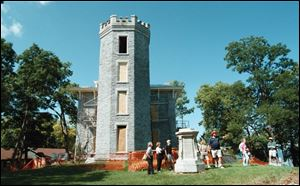 Stone Laboratory's John Hageman, in red hat, leads a tour on the grounds of Cooke's Castle.