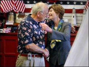 The First Lady hugs Howard Pinkley as she leaves his flag shop. During her stop here, Mrs. Bush credited success of women entrepreneurs to her husband's economic policies.