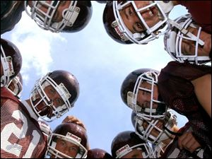 Spt  hsfoot10p  Rossford football practice.  Freshman players huddle to show their enthusiam.   Diane Hires  8/9/04