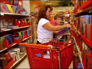 Toledoan Laurie Crawford and her son C.J. go down their list of supplies at Target on Monroe Street.