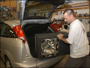 Steve Boldt fits a 15-inch speaker into a trunk, but the vehicle owner will have to keep the volumn down.