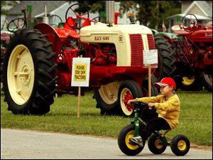 Chris Durham, 6, of Liberty Center, Ohio, rides his John Deere tricycle at the Henry County Fair.