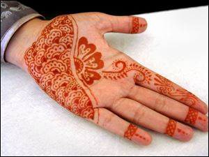 Henna-type tattoos are offered by Mehuish Durrani during the International Festival at the Islamic Center in Perrysburg.