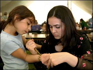 Iman Alhaj, 6, gets a tattoo from Mehuish Durrani at the International Festival at the Islamic Center of Greater Toledo.