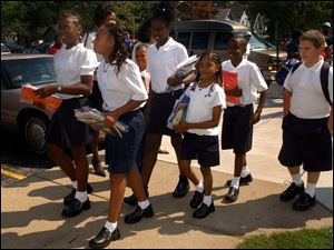 Students wearing school uniforms leave the Old West End Academy last week after the first half day of classes. This year, all TPS elementary schools will require uniforms.