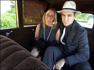 GANGSTA' WHEELS: Lisa Worthen and Paul DeRaedt 'go for a ride,' or at least pose in the back seat of a vintage auto at the Toledo Club.