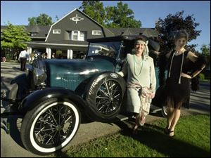 ROARING GOOD TIMES: Jane Gensler and Michelle Thomas are all dressed up in 'Flapper' outfits for the Gatsby Gala, standing next to a Gatsby-era automobile.