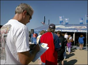 A NASCAR fan saves time by filling out a survey form as he waits in line for a free health screening at the GlaxoSmithKline facility yesterday at Michigan International Speedway.