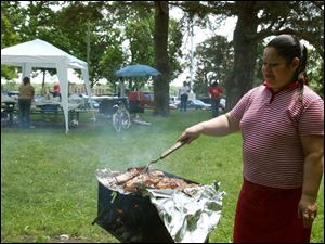Maritza Santiago grills the food at a Ponce family picnic held at Walbridge Park on Memorial Day.