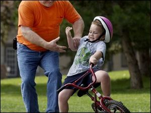 ROV September 15, 2004 - Tom Clapsaddle grabs the arm of his grandson Andrew Horton, 5, who started to fall while learning to ride a bicycle in Toledo's Walbridge Park Wednesday afternoon.  (Also helping but not in photo is Mary Clapsaddle, Andrew's grandmother and Tom's wife.)  Blade photo by Dave Zapotosky