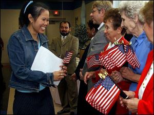 Angie Andrews, left, a native of Thailand who became a U.S. citizen at a ceremony at the Greater Islamic Center of Toledo, is greeted by women of the American Legion.