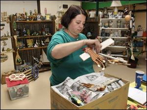 Crystal Campbell, owner of Nissi's Nautical at the Erie Street Market, packs up her merchandise for the move to the food bay. She's happy to be leaving Frog Town Square, saying the main
