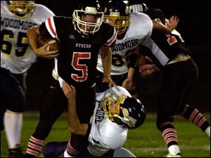 Otsego quarterback Matt Mills is brought down by Woodmore's Derek Speaker in las