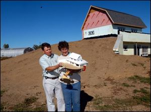 Ralph and Leah Semrock hold a model of the home they're building in Ottawa County. The home's solar panels and wind turbine will help reduce the Semrocks' energy bills.