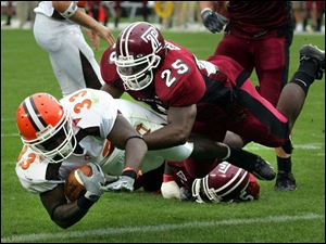 Bowling Green's P.J. Pope dives past Temple's Ryan Gore for one of his four touchdowns. Pope rushed for 106 yards on eight carries.
