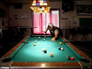 Khris Trull lines up his next shot on the pool table in the nonsmoking se