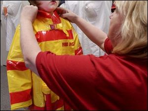 Makenna McNutt, 5, is stoic during a fitting by Costume Holiday House's Ina Blazer for a firefighter costume.