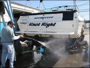 Rov boatout 3 Trevor Coleman of Toledo, sprays off his 27 foot boat at the Ottawa river yacht club as Harry Philabaum, with  Counterman marine adjust hoist . blade photo by herral long 10/6/2004