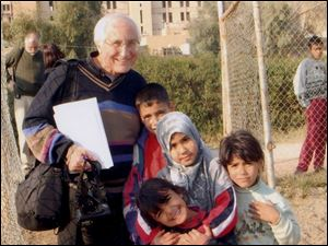 Bishop Thomas Gumbleton, shown visiting with Iraqi children in Baghdad in January, will speak in Tiffin on Thursday.