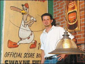 Eric Barker stands next to a Mud Hens wall hanging that his team of artists made to look like a vintage piece.