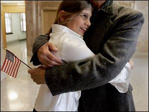 Abelardo Torres Saucedo, formerly of Mexico, is hugged by his granddaughter Christina Arnold after the ceremony.