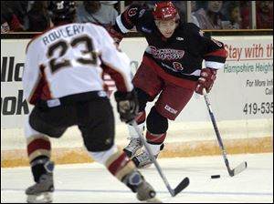 Toledo right wing Tyler Knight takes the puck up ice against Wheeling's Alex Rouleau during the first period last night.